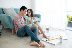 Attractive young asian adult couple planning new home design. Stock Photo