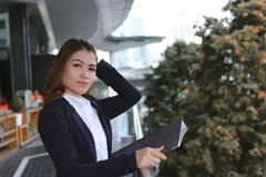 Attractive young Asian business woman standing at outside office. royalty free stock photo