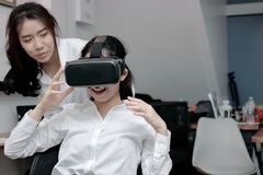 Attractive young Asian business woman wearing virtual VR reality glasses and having fun in office. Attractive young Asian business women wearing virtual VR Stock Images