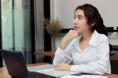 Attractive young Asian businesswoman working on the workplace in office. Thinking and thoughtful business concept. Attractive young Asian businesswoman working Royalty Free Stock Images