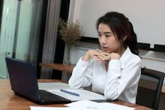 Attractive young Asian businesswoman working on the workplace in office. Thinking and thoughtful business concept stock photos