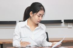 Attractive young Asian businesswoman working on the workplace in office. Thinking and thoughtful business concept. stock images