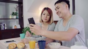 Attractive young Asian couple distracted at table with newspaper and cell phone while eating breakfast. stock video footage