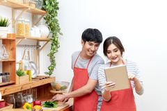 Attractive young asian couple or student looking at recipe and enjoy cooking food in kitchen at home. Man and woman in gen royalty free stock image