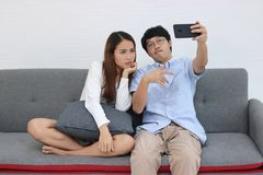 Attractive young Asian couple taking a photo or selfie together in living room. Love and romance people concept stock photo