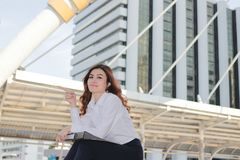 Attractive young Asian employee sitting on staircase after work and positive look at urban building background. Attractive young Asian employee sitting on Royalty Free Stock Photos