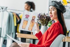 Asian fashion designer with sketches. Attractive young asian fashion designer holding sketches and looking away stock images