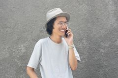 An attractive young asian man with hat and glasses using smarphone stock image