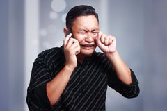 Young Man Getting Bad News on Phone, Shocked and Crying. Attractive young Asian man talking on his phone, getting bad news, shocked and crying gesture Stock Images
