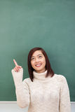 Attractive young Asian student pointing upwards Stock Photography