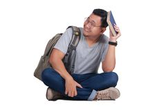 Young Student Reading Book Regret Sad Gesture. Attractive young Asian student reading book while sitting on the floor, isolated on white, sad regret failure Royalty Free Stock Image