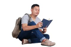 Young Student Reading Book, Happy Smiling Gesture. Attractive young Asian student reading book while sitting on the floor, isolated on white, smiling happy Stock Images