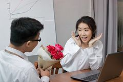 Attractive young Asian woman excited to get a bouquet of red roses in office on valentine`s day. Love and romance in workplace co Royalty Free Stock Photos