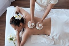 Attractive young Asian woman smiling and getting Spa treatment on white bed stock image