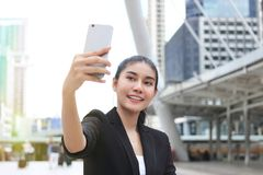 Attractive young Asian woman taking a photo or selfie with mobile smart phone on street of modern city. Royalty Free Stock Image