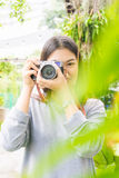 Attractive young asian woman talking pictures outdoors Stock Photos