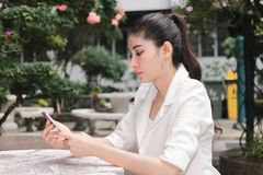 Attractive young Asian woman using mobile smart phone. Internet of things concept.  stock photos