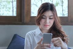 Attractive young Asian woman using mobile smart phone at living room royalty free stock photography
