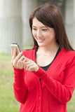 Attractive young Asian woman using smartphone Royalty Free Stock Images