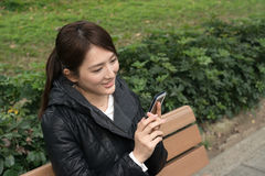 Attractive young Asian woman using smartphone Stock Photography