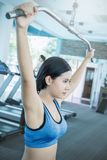 Attractive young asian woman working out with exercise machine at the gym stock photos