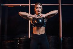 Attractive young athlete with muscular body exercising crossfit. Woman in sportswear doing crossfit workout with kettle