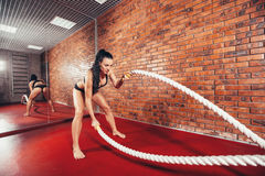 Attractive young and athletic girl using training. An attractive young and athletic girl using training ropes in a gym. on the background wall of red brick Stock Images