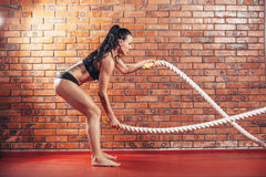 Attractive young and athletic girl using training. An attractive young and athletic girl using training ropes in a gym. on the background wall of red brick Stock Photography