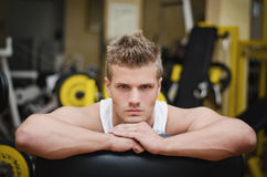 Attractive young athletic man resting on gym equipment Stock Photos