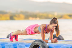 Attractive young athletic woman exercising outdoor in summer sunrise Stock Photos