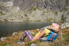 Attractive young backpacker relaxing at a lake Stock Images