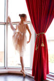 Attractive young ballerina a window Stock Photography