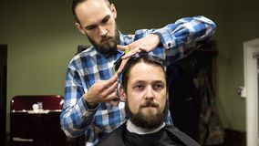 Attractive young barber is cutting human hair with the scissors. He is looking at hair with concentration. The bearded stock video footage