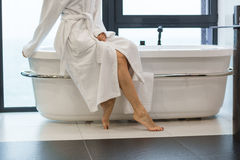 Attractive young barefooted woman in white bathrobe sitting on bathtub Stock Photography