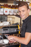 Attractive young barista making coffee. Royalty Free Stock Photos