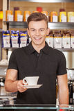 Attractive young barista offering coffee. Royalty Free Stock Photo