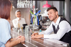 Attractive young barman is flirting with female Royalty Free Stock Image