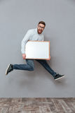 Attractive young bearded businessman holding copyspace board jumping Royalty Free Stock Images