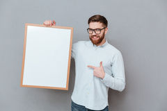 Attractive young bearded businessman holding copyspace. Image of attractive young bearded businessman holding copyspace board and pointing standing over grey Stock Photo