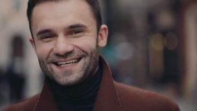 An attractive young bearded man in casual outfit happily smiling towards the camera. Male beauty. Urban life, active. Lifestyle. City lights on the background stock video footage