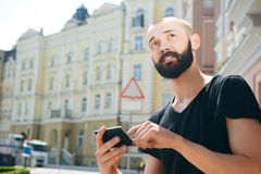 Attractive young bearded man got lost in city Royalty Free Stock Images
