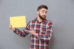Attractive young bearded man holding copyspace blank. Image of attractive young bearded man holding copyspace blank standing over grey background and pointing Royalty Free Stock Photography
