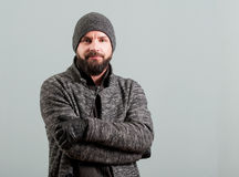 Attractive young bearded man keeping arms crossed and smiling Stock Photo