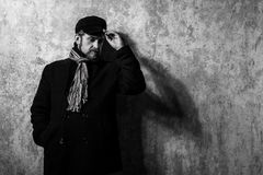 Attractive young bearded man in a pea coat. And cap is standing at the wall Royalty Free Stock Images