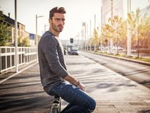 Attractive young man portrait in city street. Attractive young bearded man portrait in urban environment, in a street, looking at camera Royalty Free Stock Photos