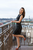 Attractive young beautiful girl wearing classical black dress posing on the balcony of luxury building. Stock Image