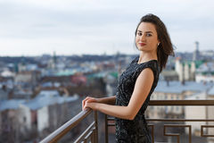 Attractive young beautiful girl wearing classical black dress posing on the balcony of luxury building. Royalty Free Stock Photography