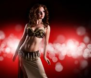Attractive bellydancer in front of light background royalty free stock photography