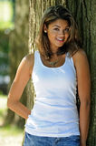 Attractive Young Biracial woman portrait. Portrait of young biracial woman in white tank top and jeans - next to tree royalty free stock photography