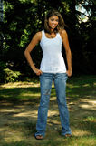 Attractive Young Biracial woman portrait. Portrait of young biracial woman in white tank top and jeans - next to tree royalty free stock images